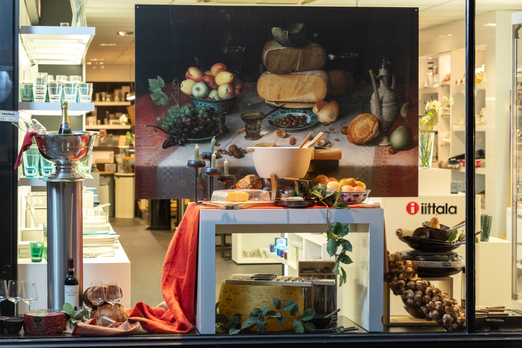 Above: Cheese related products in La Cuisine's window display complement the cheese in the artwork.